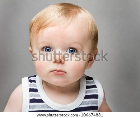 Toddler against a medium to dark grey  background. Very bright eyed and adorable - stock photo