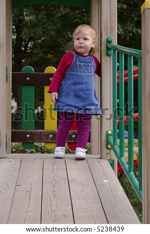 Toddler baby girl standing on wooden playground - stock photo