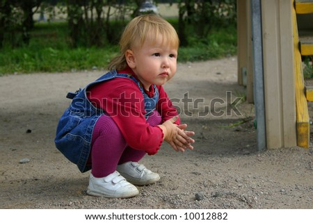 Toddler blondie girl wearing jeans dress playing with sand in summer day