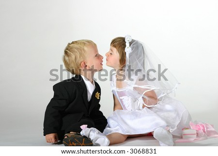 Toddler boy and girl dressed like groom and bride kissing - stock photo