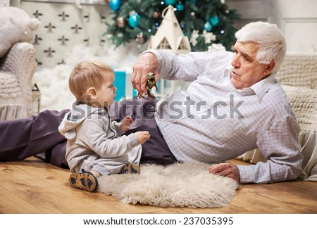 Toddler boy and his grandpa playing with toy dinosaur at Christmas tree - stock photo