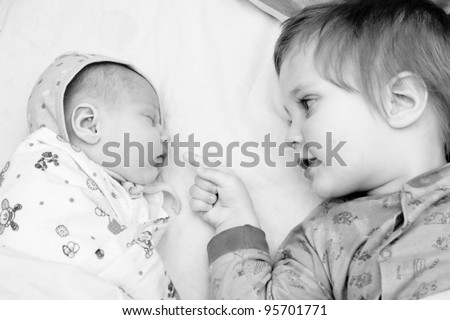 Toddler boy and his newborn sister are lying on a bed. Black  and white photo - stock photo