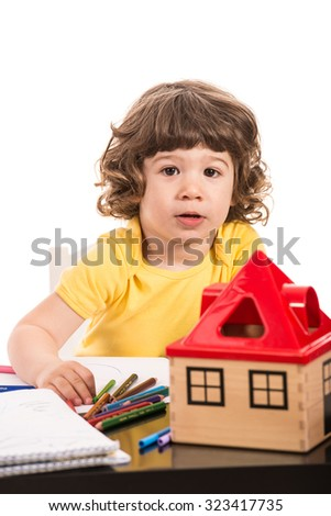 Toddler boy at kindergarten sitting on chair at table with materials isolated on white background - stock photo