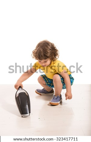 Toddler boy cleaning house with hand-held vacuum cleaner