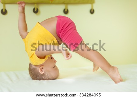 Toddler boy doing exercises in child room - stock photo