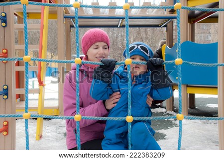 Toddler boy enjoys climbing up a rope ladder with his mother in a children's playground - stock photo