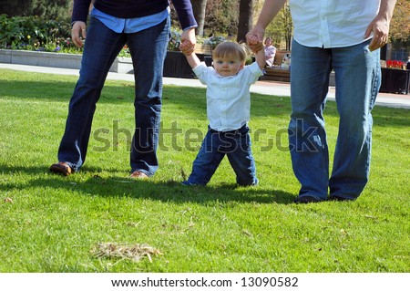 Toddler boy holding hands and walking with his parents through a park.  Only the legs of the parents are in the frame. - stock photo