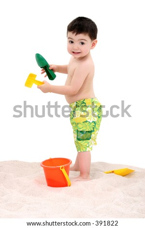 Toddler boy in swim suit playing in the sand. - stock photo