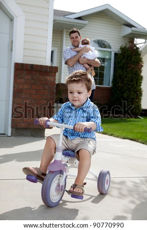 Toddler boy learning to ride tricycle with father in background - stock photo
