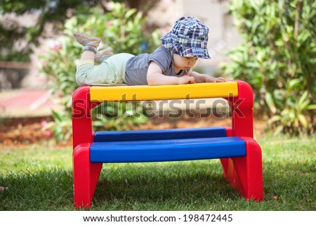 Toddler boy playing while lying on kids table outdoors - stock photo