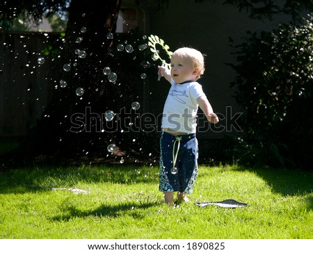 Toddler boy playing with bubbles - stock photo