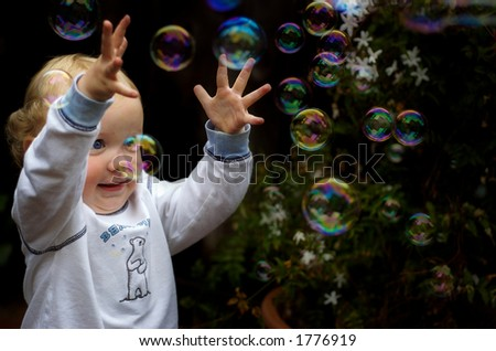 toddler boy playing with bubbles two - stock photo