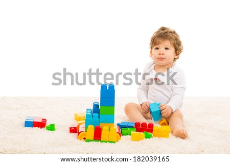 Toddler boy playing with building blocks and sitting on fur carpet home