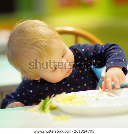 Toddler boy playing with food at the indoors cafe - stock photo