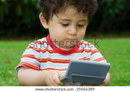 toddler boy playing with mini laptop computer