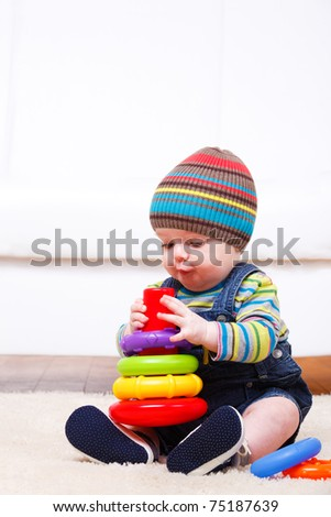 Toddler boy playing with pyramid - stock photo