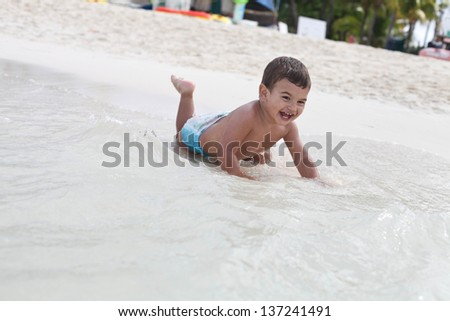 toddler boy playing with waves on the beach - stock photo