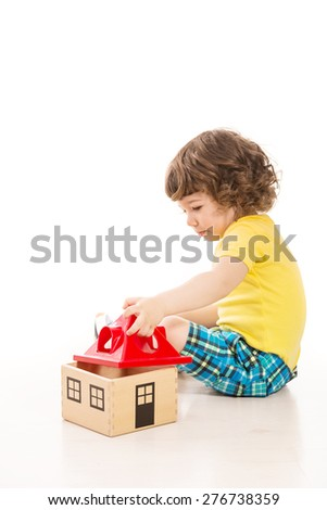 Toddler boy playing with wooden house against white background - stock photo