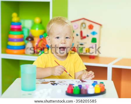 Toddler boy practice to paint on paper sitting at the table in child room - stock photo