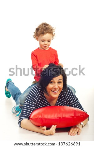 Toddler boy riding his mother and playing together home