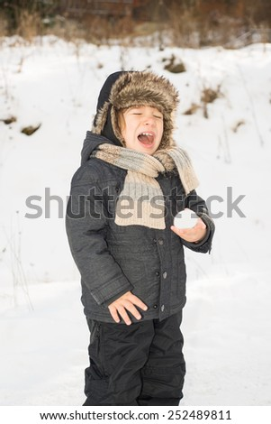 Toddler boy  screaming  because holding a snow ball in the hand for first time and it is too cold - stock photo