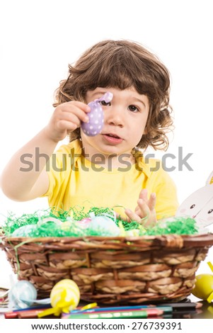 Toddler boy showing lilla easter egg from basket isolated on white background - stock photo