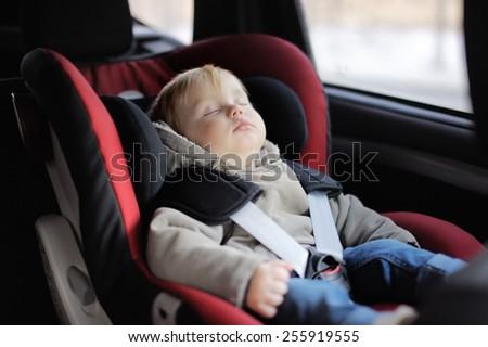 Toddler boy sleeping in car seat - stock photo