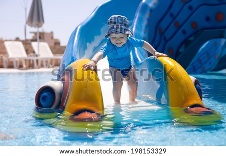Toddler boy standing at the bottom of water slide in a swimming pool - stock photo