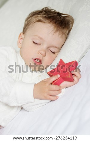Toddler boy sweetly sleeping with a toy on a white background - stock photo
