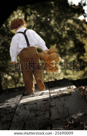 Toddler boy walking away with teddy