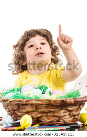 Toddler boy with Easter basket pointing up to copy space isolated on white background - stock photo