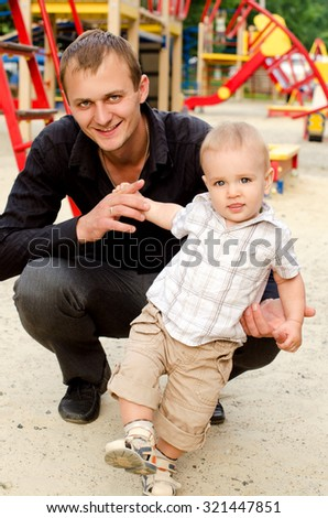 toddler boy with his smiling daddy on playground outdoors - stock photo