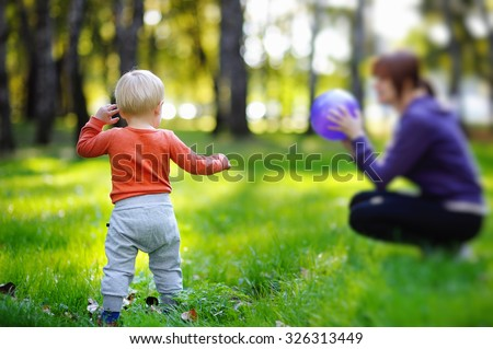 Toddler boy with his young mother playing with ball at sunny park - stock photo