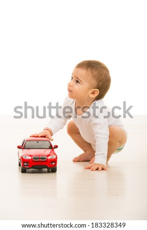 Toddler boy with toy car looking away in home