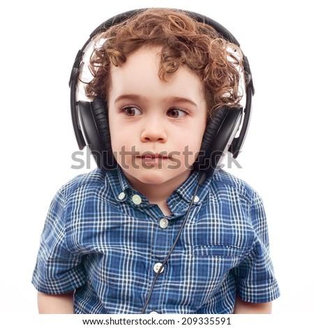 Toddler carefully listening to something in headphones - stock photo