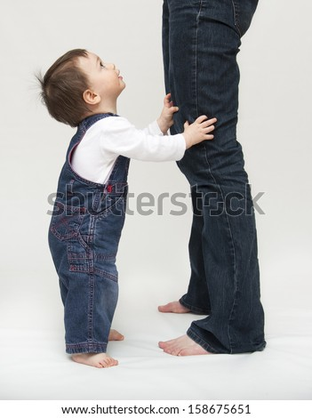 Toddler child, boy or girl, standing by mother's legs, looking up - stock photo