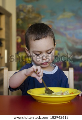 Toddler child eating soup at table at home or at kindergarten.  - stock photo
