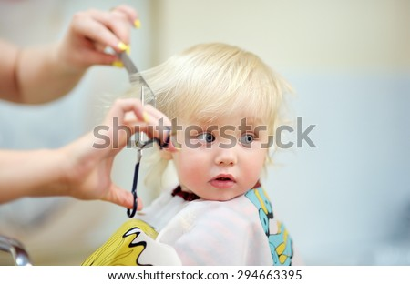 Toddler child getting his first haircut  - stock photo