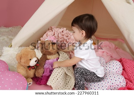 Toddler child, kid, engaged in pretend play with stuffed toys, and teepee tent - stock photo