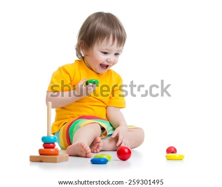 toddler child playing with colorful toy pyramid - stock photo