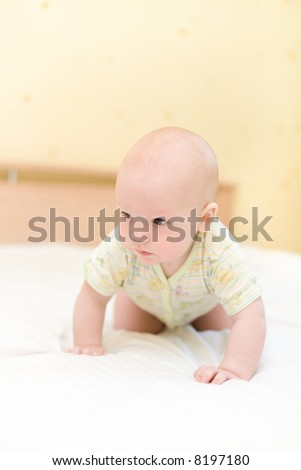 Toddler crawling on bed - stock photo