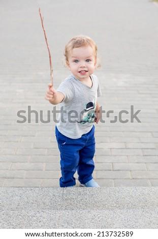 Toddler cute boy walking holding a stick - stock photo