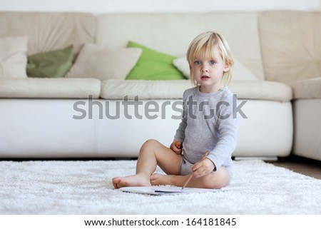 Toddler drawing pictures sitting on a carpet at home - stock photo