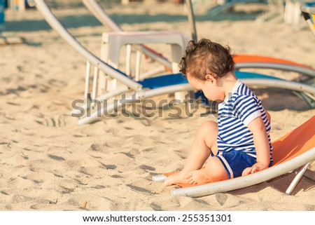 Toddler dressed as a sailor sitting on a tilted sunbed and exploring the sand on a beach. Photo with untraditional color rendering for artistic look