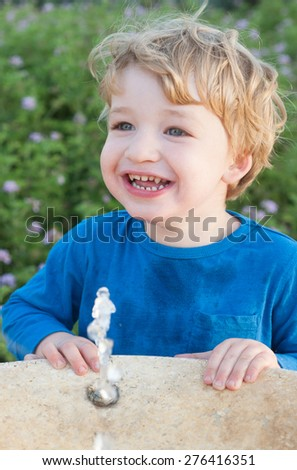 Toddler drinking from the water fountain in the summertime  - stock photo
