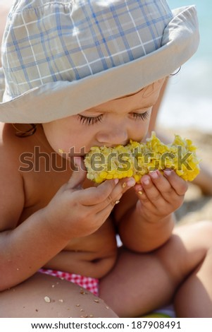 toddler eating corn on the beach - stock photo