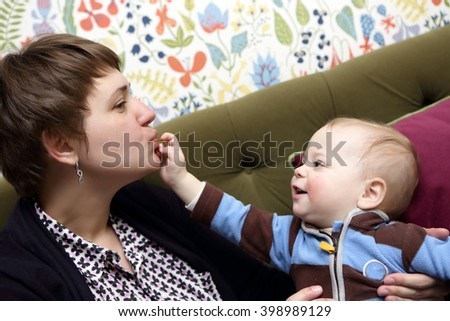 Toddler feeding his mother on the sofa - stock photo