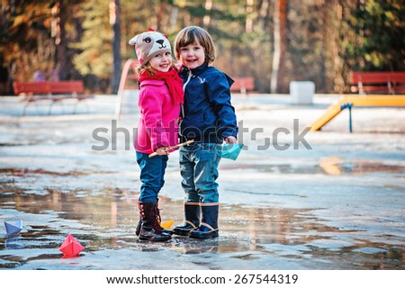 toddler friends are happy together playing in spring puddle with paper boats - stock photo