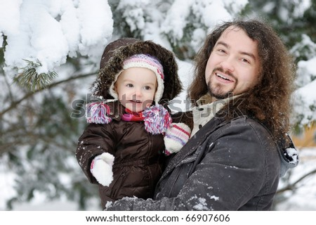Toddler girl and her father on beautiful snowy winter day