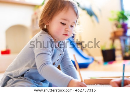 Toddler girl drawing picture in her house
